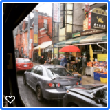 Toronto's Chinatown with stores along the sidewalk & parked cars