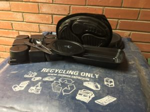 variety of black plastic containers and cutlery on the lid of a large, blue recycling bin
