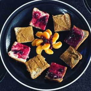 Squares of toast spread alternately with jam and almond butter on a plate with orange segments and cranberries in the centre.