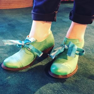 A pair of feet in tie-up blue-green shoes by John Fluevog